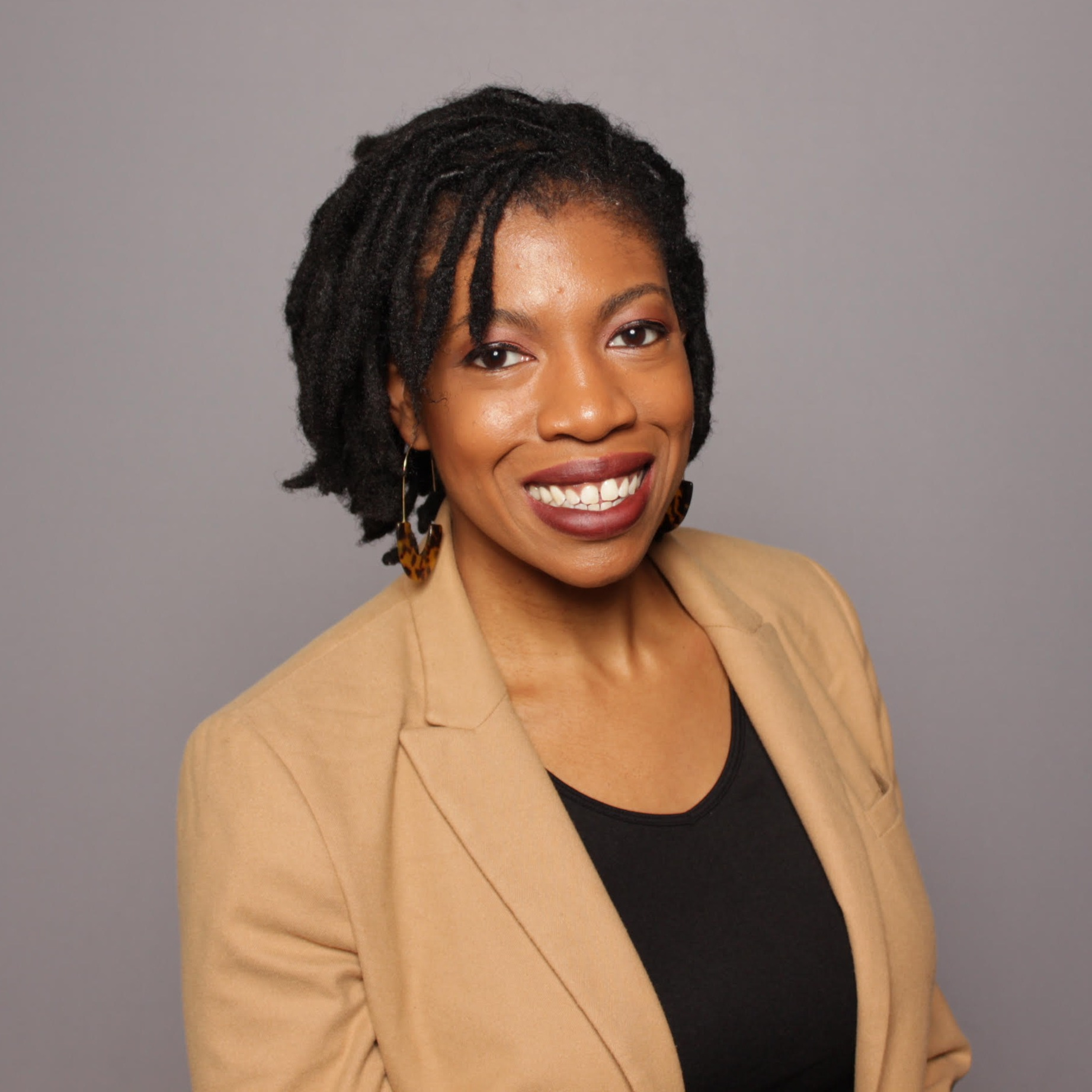 Andrea Tatum, a Black woman with short black hair and tan suit jacket.