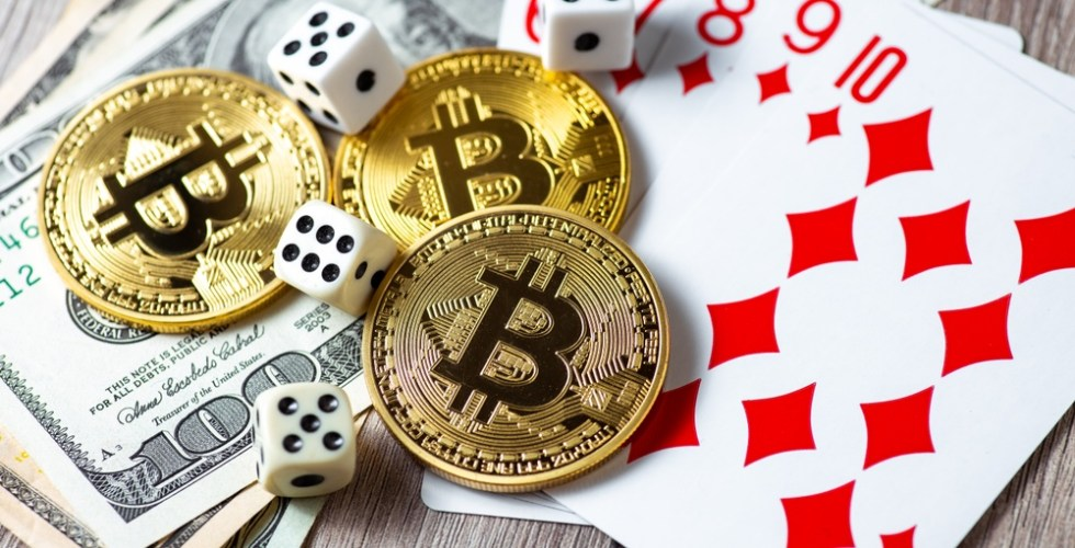 Bitcoins, cards, dices on wooden background. Cryptocurrencies gambling concept