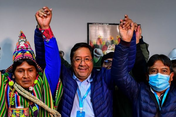 Bolivia's leftist presidential candidate Luis Arce (C), of the Movement for Socialism party, celebrates with running mate David Choquehuanca (R) early on October 19, 2020, in La Paz, Bolivia. - Bolivian presidential candidate Luis Arce, the leftist heir to former leader Evo Morales, appeared headed to a first-round election victory on October 18, 2020 with 52.4 percent of the vote, according to an authoritative exit poll from TV station Unitel. (Photo by RONALDO SCHEMIDT / AFP)