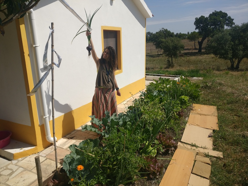Laetitia, holding the first onions that she grew at her home in the countryside outside Lisbon