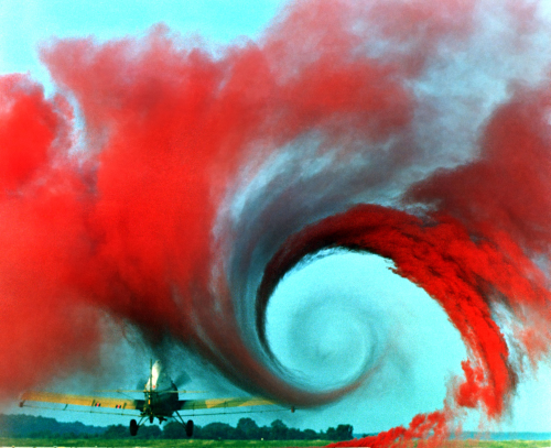 Red smoke showing the wind vortex behind an airplane