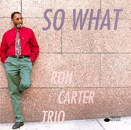 Album cover for Ron Carter Trio, Ron Carter wearing a red shirt and green pants, leaning against a stone wall, with the album name in print, So What
