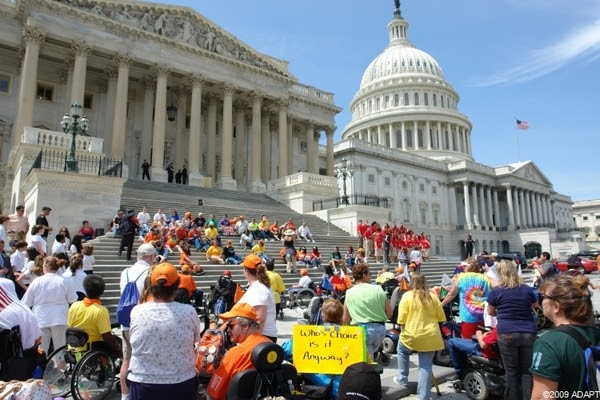 Large ADAPT protest at the National Capitol with many participants with disabilities