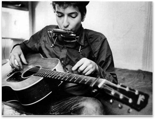 Early Picture of Bob Dylan playing an acoustic guitar and harmonica.