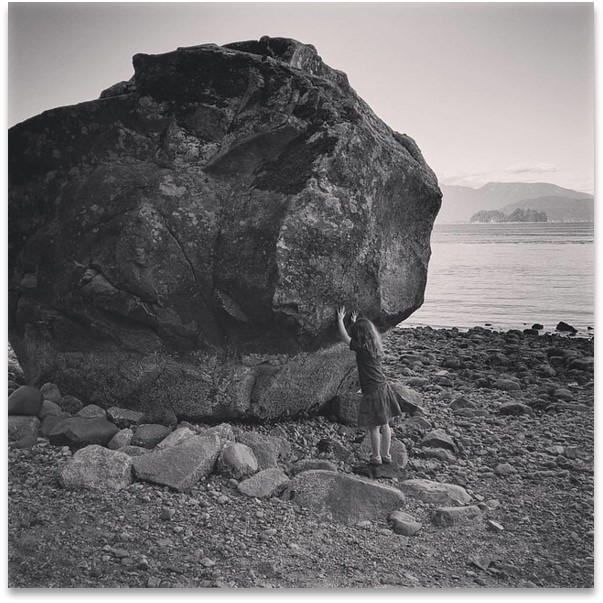 Black and White photo of a small child trying to move a large boulder.