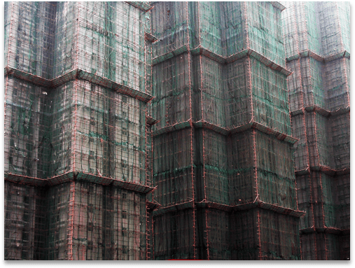A large and tall building entirely surrounded by bamboo scaffolding