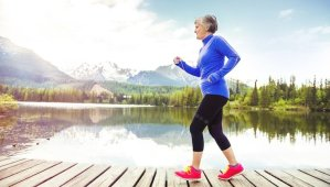 Older woman with red shoes walking on wooden path with lake and mountains in background