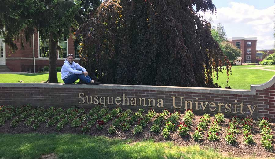 Dr. Bill Thomas sitting on entrance sign at Susquehanna University