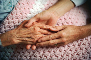 2 hands embracing the hand of an older person