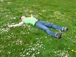 man relaxing laying in the grass facing the sky