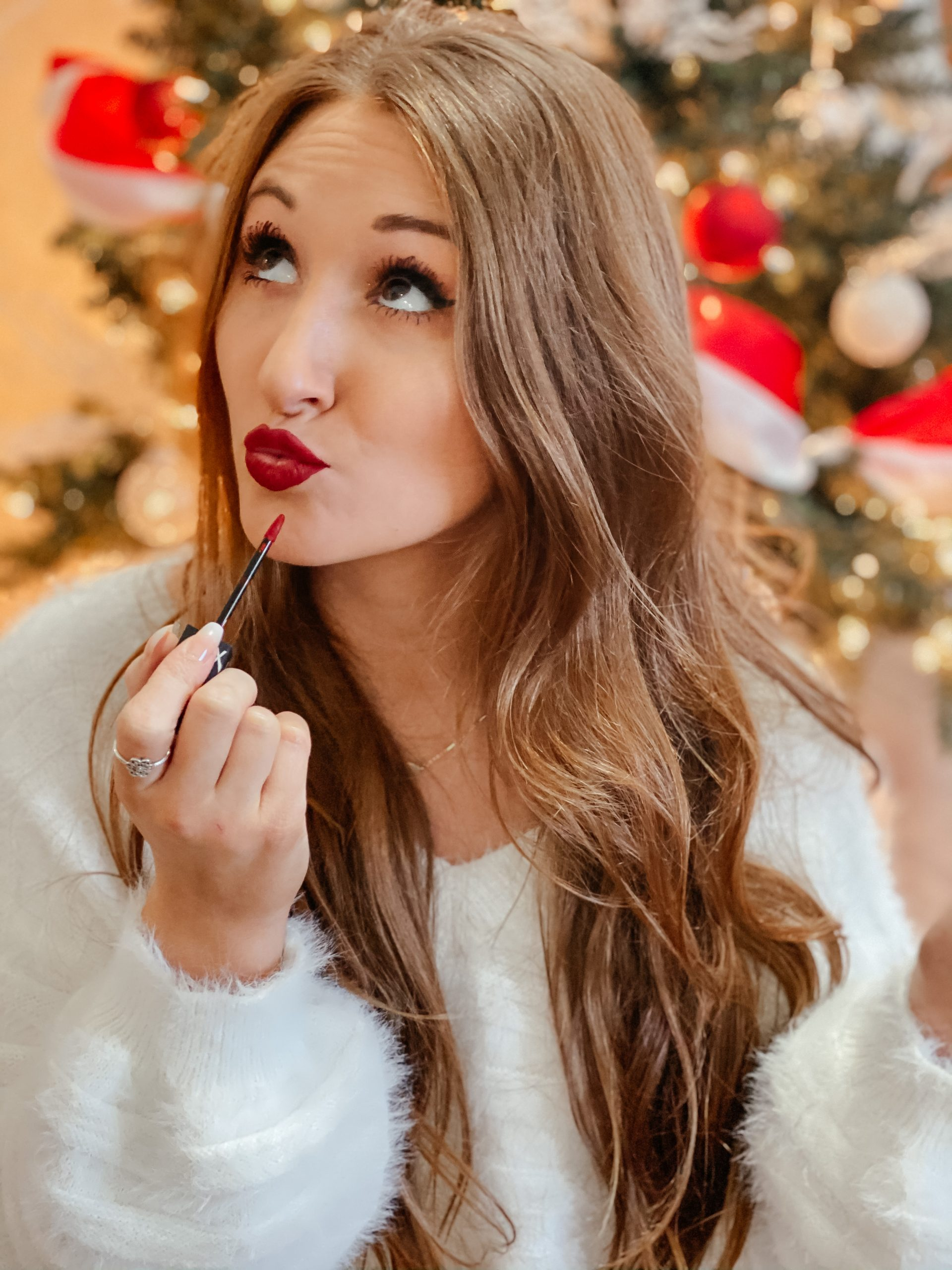 White eyelash sweater with red lipstick and black Spanx faux leather leggings in front of a Christmas tree