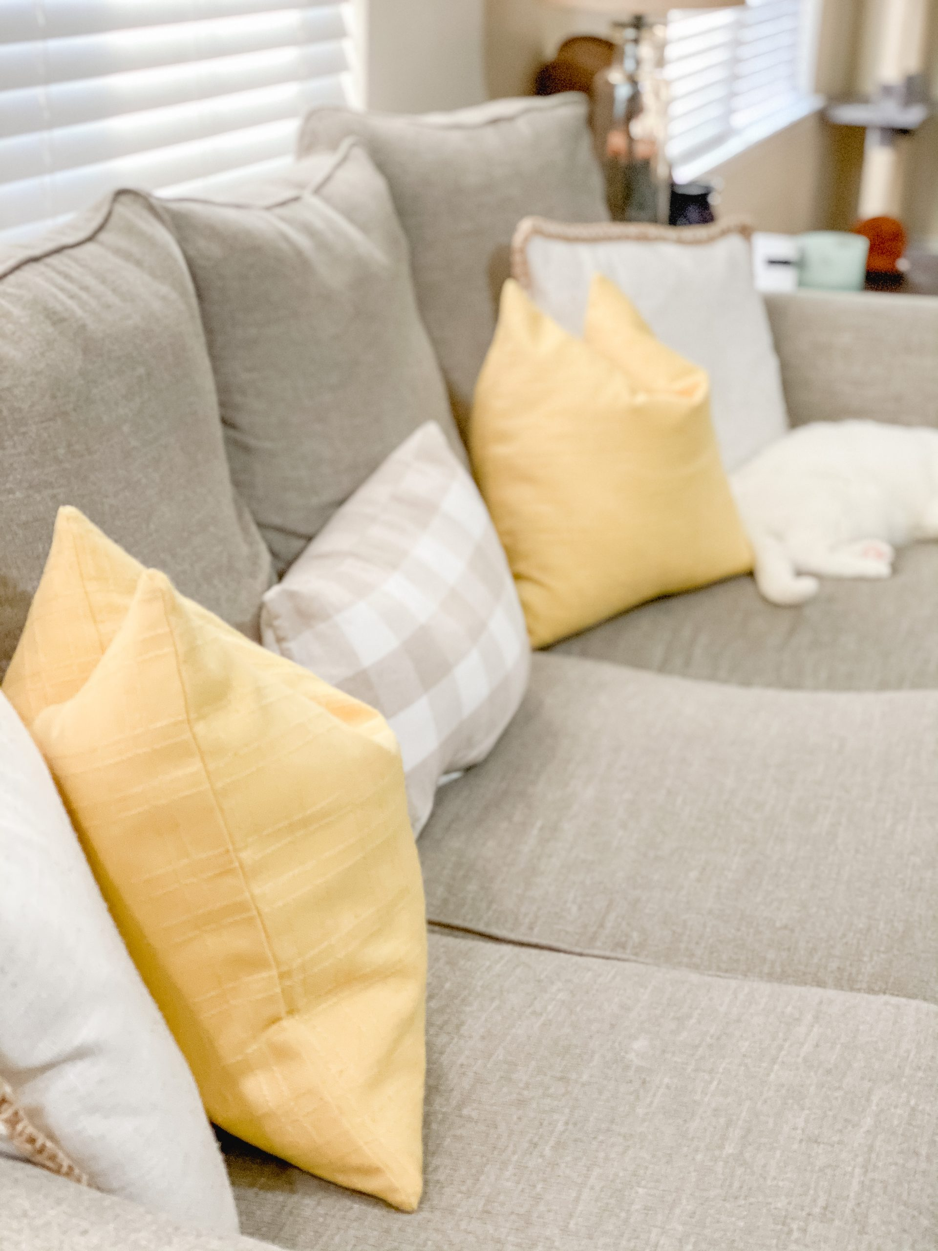 Spring decor in living room with yellow throw pillows.
