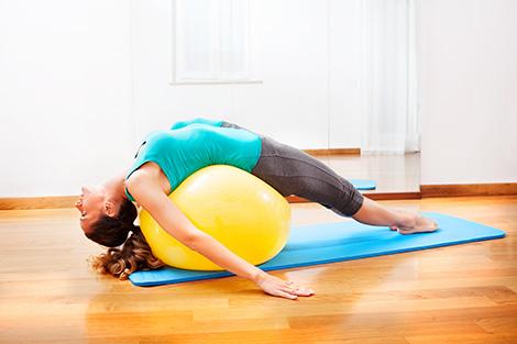 Teacher making body exercises on a yellow ball