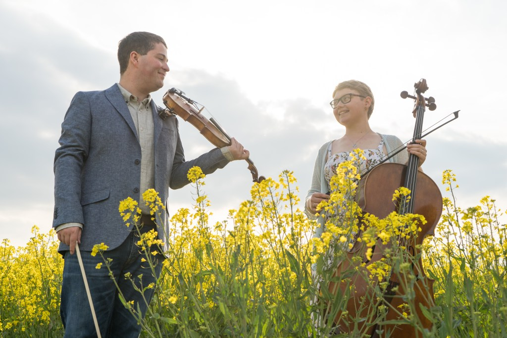 Jaya Hanley Violinist and Sarah James Cellist of the Chapel Hill Duo enjoy the sun in a field of yellow rapeseed flowers silhouette framed with cloudy background.