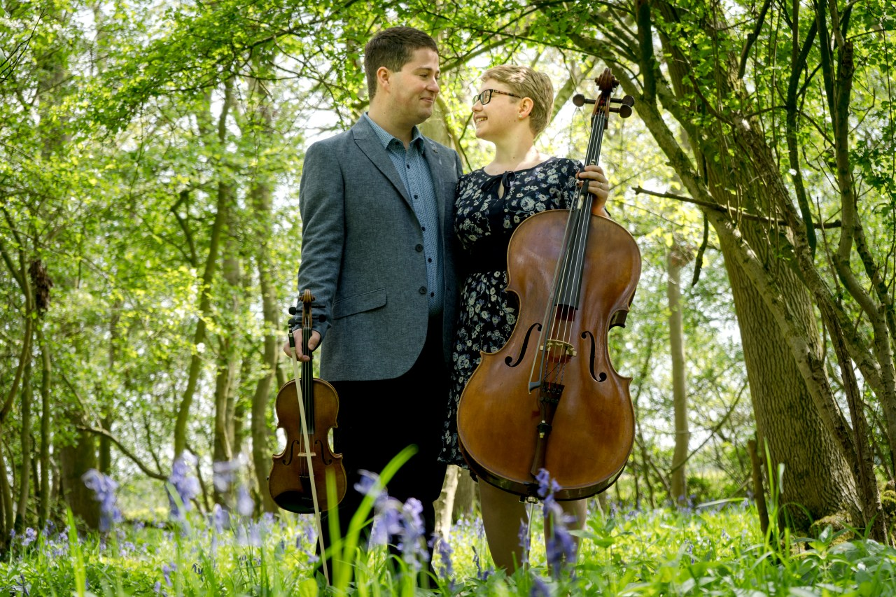 Violinist Jaya Hanley and Cellist Sarah James look at each other romanitcally in a bluebell wood. The Chapel hill Duo.