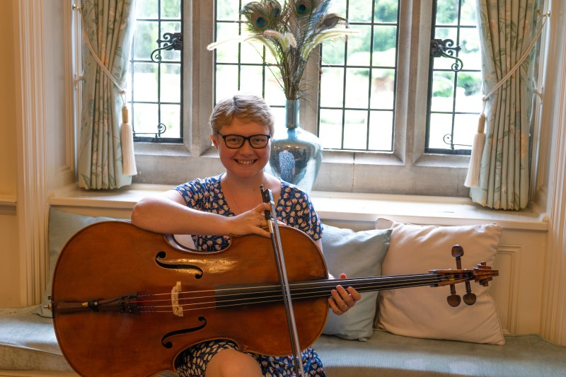 Cellist Sarah James on a window seat in the ceremony room at Lanwades Hall.