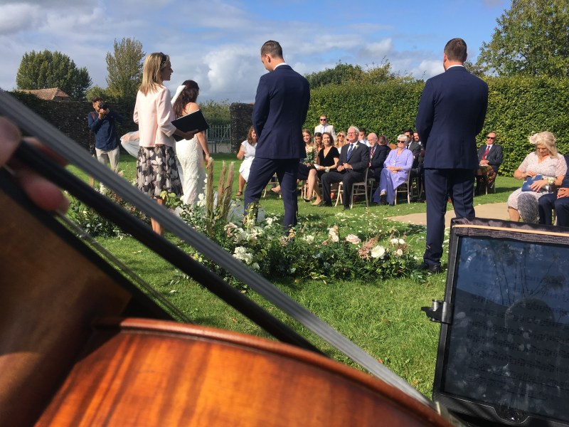 An outdoor wedding ceremony with celebrant from Cellist Sarah James point of view.
