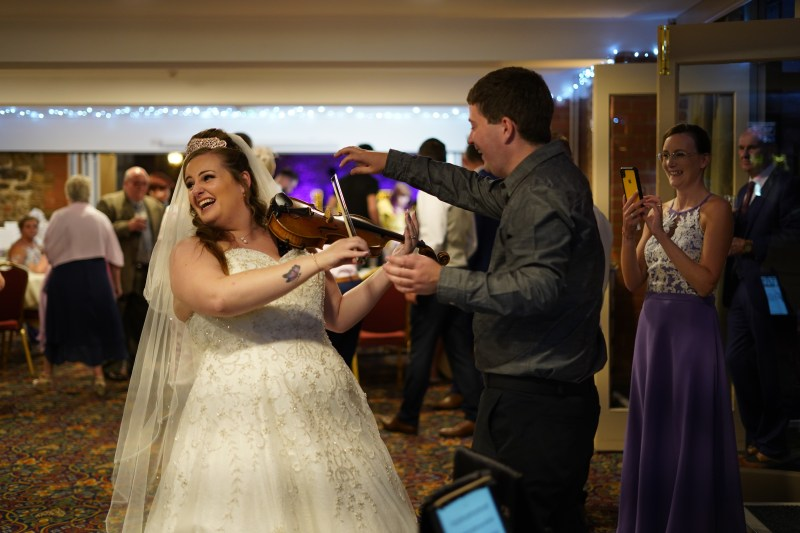 Violinist jaya hanley giving a violin lesson to a bride on her wedding day. Bride laughing.