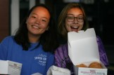 Student Council Representatives Michelle Lee (10) and Susie Browder (10) hand out donuts under the bus canopy.