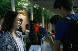 Student Council Representative Sylvia Tang (12) hands out donuts under the bus canopy.