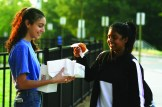 Student Council Representative Noreen Ali (10) hands out a donut to Sarah Thangamani (10) at the Front Office.