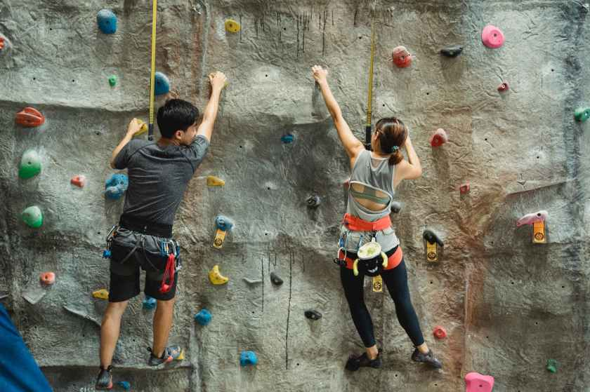 young fit sporty couple training on climbing wall