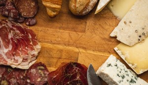 An assortment of meats and cheeses on a wood charcuterie board.