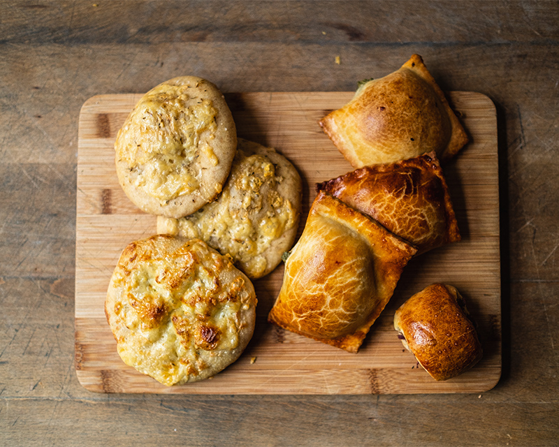 A variety of fresh baked savoury goods on a wood board.