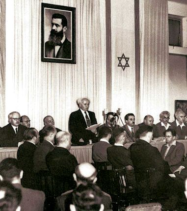 David Ben-Gurion (First Prime Minister of Israel) publicly pronouncing the Declaration of the State of Israel, May 14 1948, Tel Aviv, Israel, beneath a large portrait of Theodor Herzl. Photo by, Rudi Weissenstein.