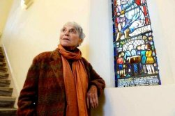 """Professor Eva Haller, one of Jane Haining's """"girls,"""" who said she owed her life to her mentor standing by one of the stained glass windows dedicated to the matron at Queen's Park Govanhill Parish Church in Glasgow."""