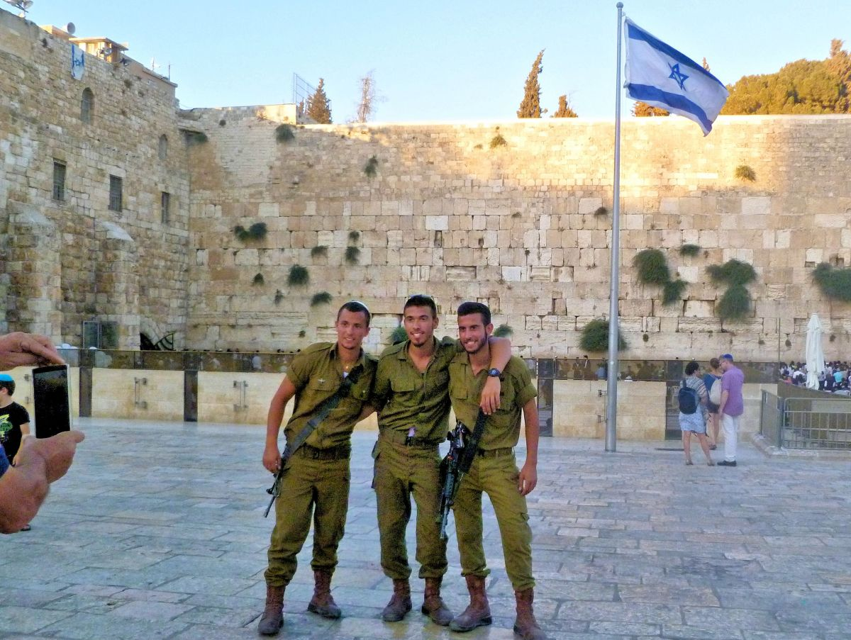 Three friends pose at the Western Wall, Jerusalem.