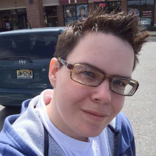 Self portrait in front of a salon, sporting a fauxhawk and brown eyeglasses.