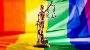 A statuette of Lady Liberty standing upon the Pride flag.