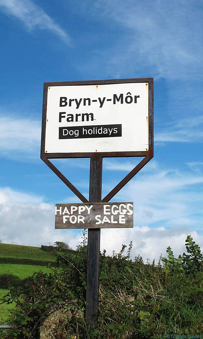 Farm sign near Kidwelly on The Wales Coast Path, photographed by Charles Hawes. Walking in Wales.