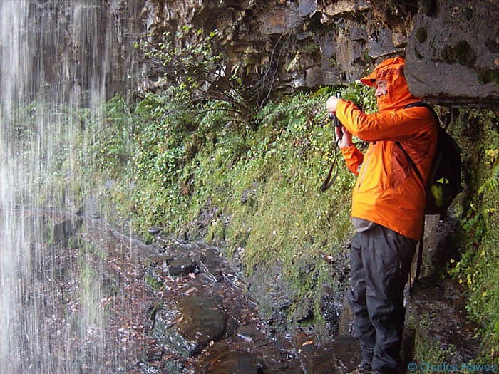 Charles Hawes inside the Sgwd yr Eira waterfall on the River Hepste in Powys, Wales. Photograph by Paul Steer. Walking in wales.