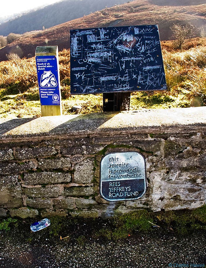 Vanadalised board by the road over Blorenge photographed by Charles Hawes. Walking in Wales.