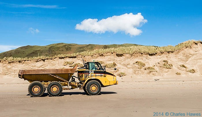 Truck moving sand at Aberdovey beach, photographed from the Wales Coast Path by Charles Hawes