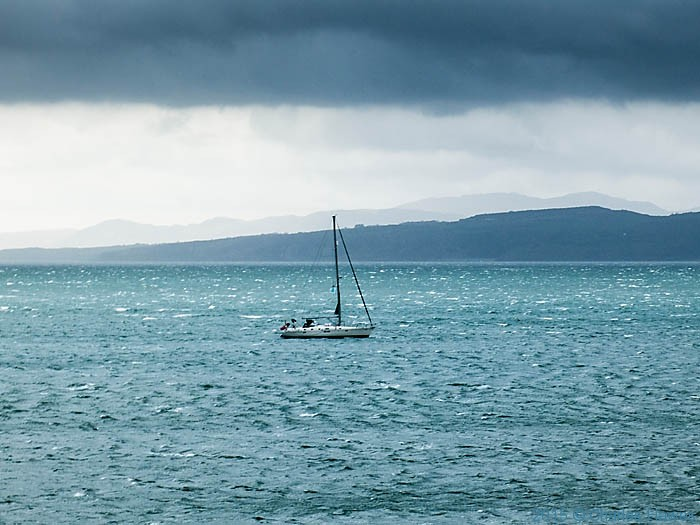 Boat in Moelfre Bay, photographed from the Wales Coast Path on Anglesy by Charles Hawes