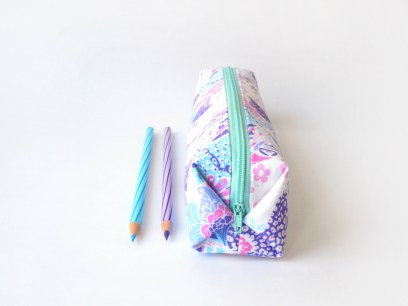 Pencil case in white with flowers and batik-like patterns in blue, pink and purple