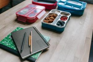 school lunch in bento box along with school supplies