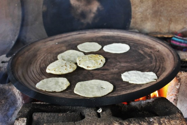 Tortillas cooking on an open fire