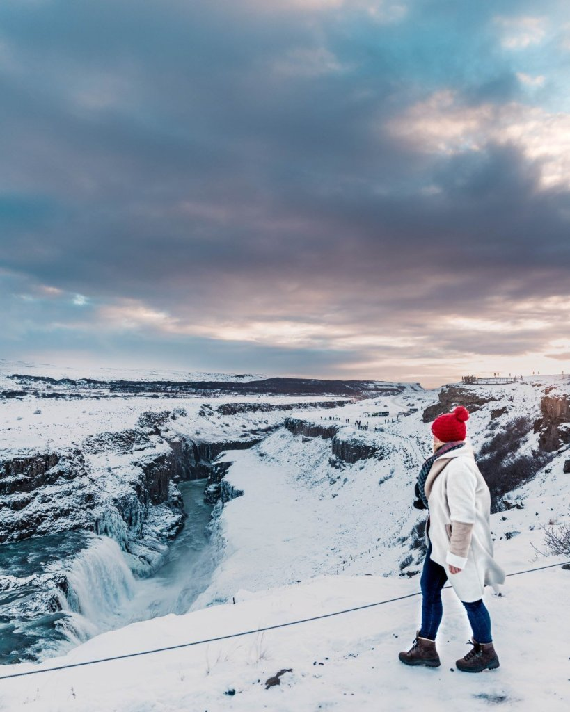 Woman in red hat overlooking Gulfoss waterfall in Iceland