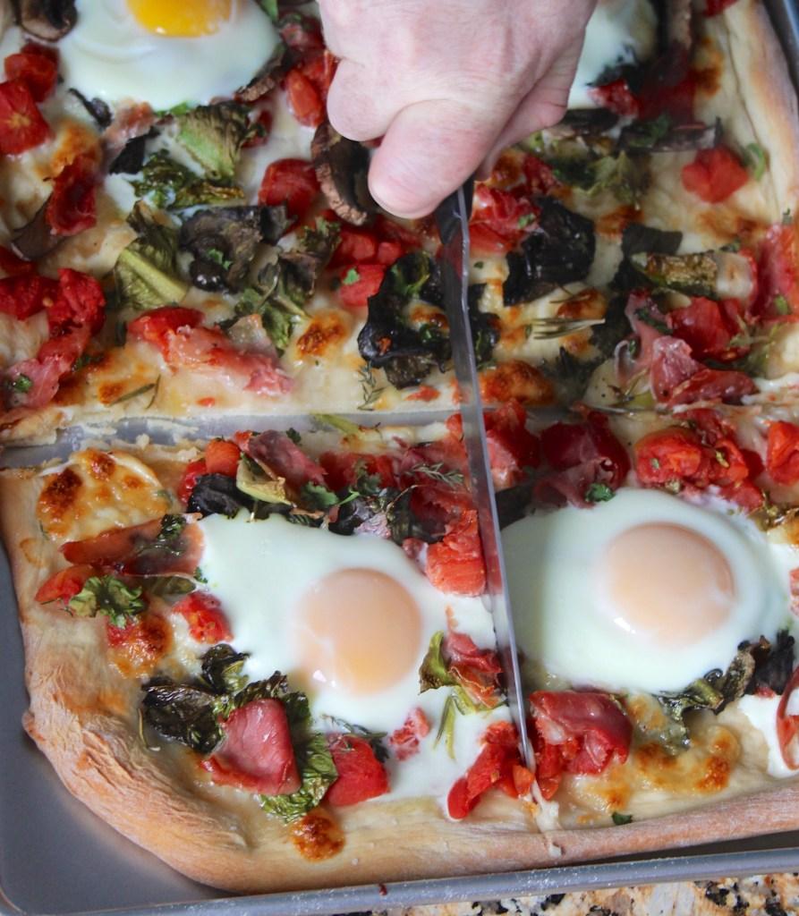 slicing breakfast pizza