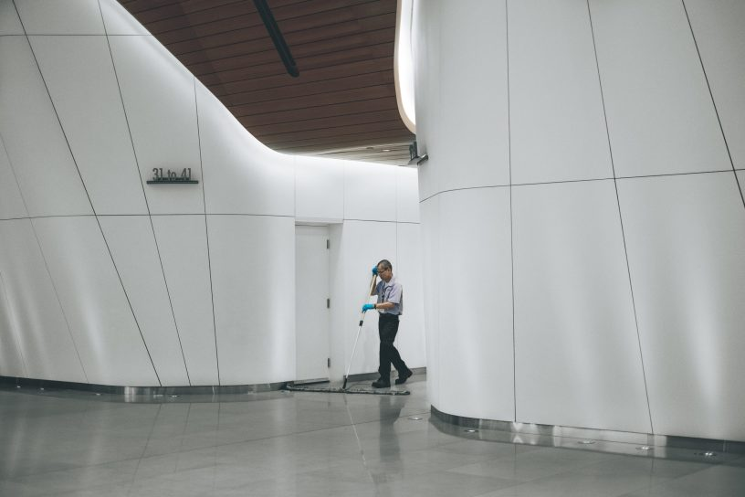 Janitor Cleaning Building Hallway