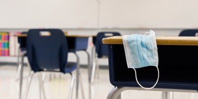 Protective surgical mask resting on top of a student desk within a clean contemporary classroom