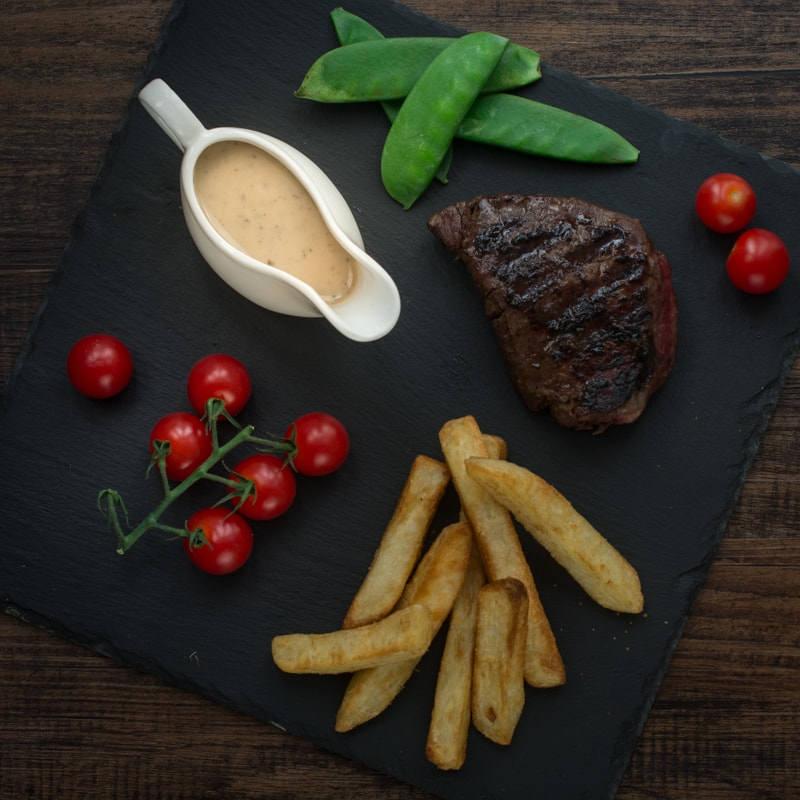 Looking down on a slate with a white jug of peppercorn sauce, cherry tomatoes, mangetout, chunky chips and steak.