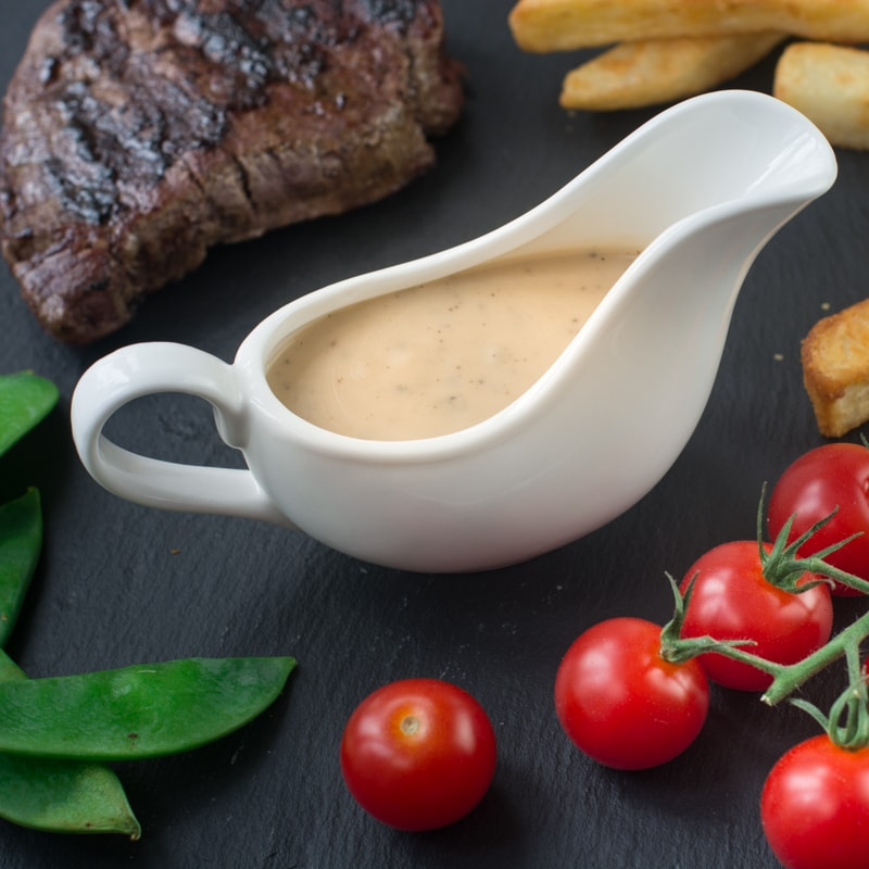 A small white jug of peppercorn sauce on a slate surrounded by steak, mangetout, cherry tomatoes on the vine and chunky chips.