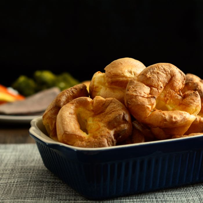A blue serving dish full of freshly made Yorkshire puddings with a plate of roast dinner in the background.