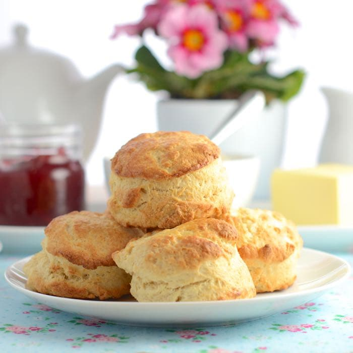 A stack of plain scones on a plate with tea, jam an flowers in the background.