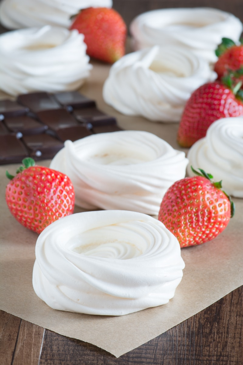 Meringue nests with fresh strawberries and a block of dark chocolate.